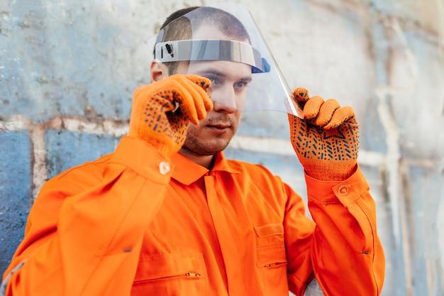 Werknemer in uniform met gelaatsscherm en beschermende handschoenen