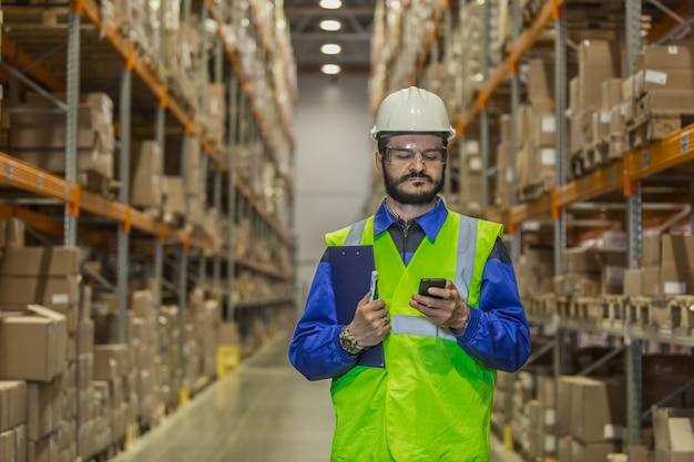 Werknemer in uniform met mobiele telefoon in magazijn
