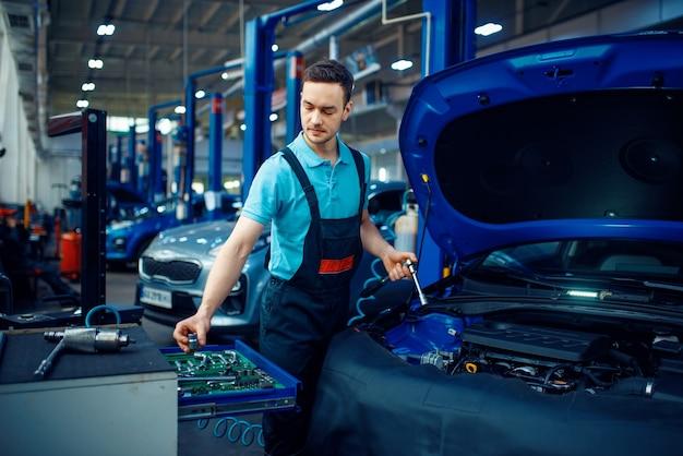 Werknemer in uniform neemt moersleutel uit gereedschapskist, autoservicestation. automobielcontrole en inspectie, professionele diagnostiek en reparatie