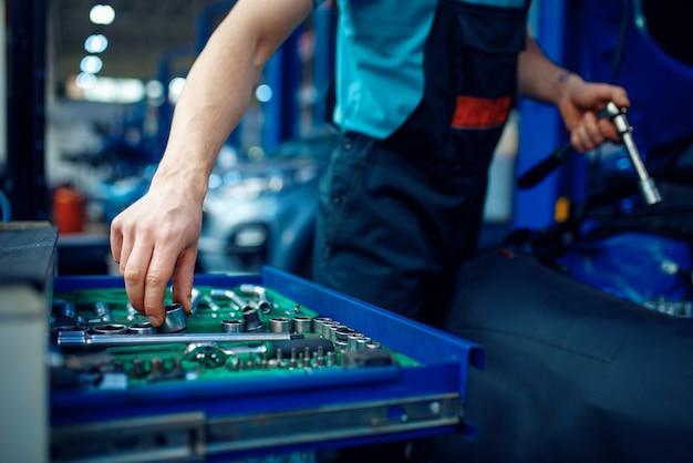 Werknemer in uniform neemt moersleutel uit gereedschapskist, autoservicestation.
