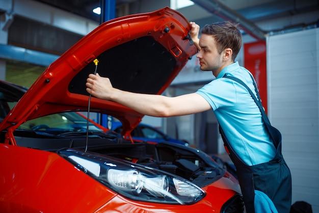 Werknemer in uniform opent motorkap, auto servicestation. automobielcontrole en inspectie, professionele diagnostiek en reparatie