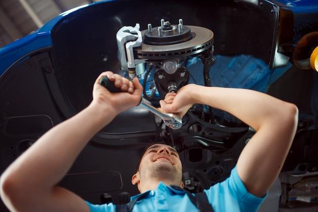 Werknemer in uniform reparatie voertuig op lift, auto servicestation. automobielcontrole en inspectie, professionele diagnostiek en reparatie