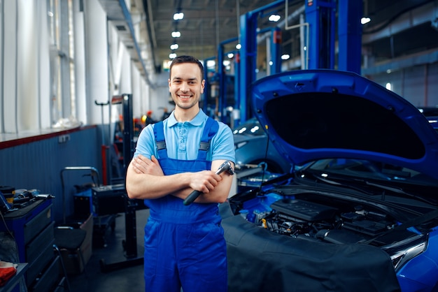 Werknemer in uniform staat op het voertuig op de lift, auto servicestation. automobielcontrole en inspectie, professionele diagnostiek en reparatie