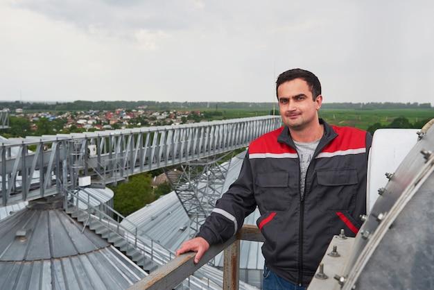 Werknemer in uniform tegen de agri-gebouwen op de achtergrond