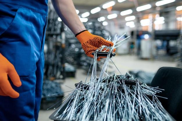 Werknemer in uniform toont nieuwe fietsspaken op fabriek. montage van fietswielen in de werkplaats, installatie van fietsonderdelen
