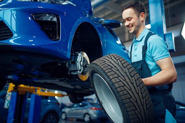 Werknemer in uniform verwijdert wiel uit voertuig, autoband servicestation. automobielcontrole en inspectie, professionele diagnostiek en reparatie