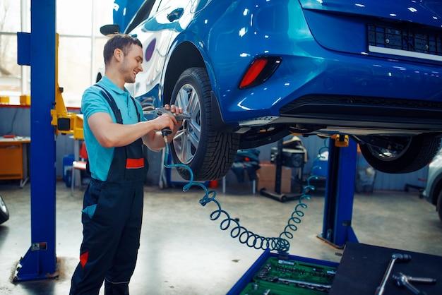Werknemer in uniform verwijdert wiel uit voertuig op lift, autoband servicestation. automobielcontrole en inspectie, professionele diagnostiek en reparatie