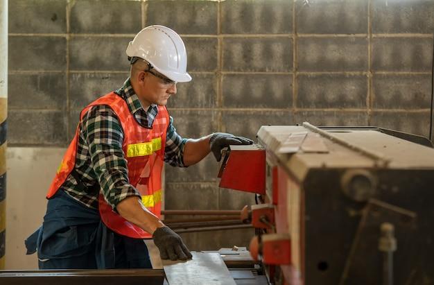 Werknemer in uniform werken in handmatige draaibank in de metaalindustrie fabriek