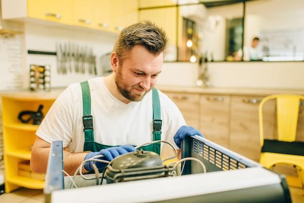 Werknemer in uniforme reparaties koelkast compressor thuis.