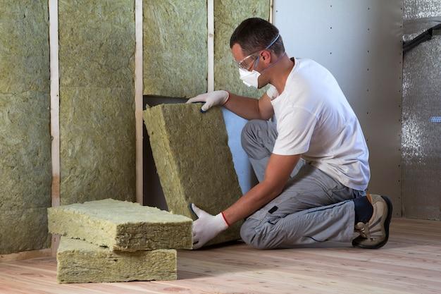 Werknemer in veiligheidsbril en masker renovatie huis interieur