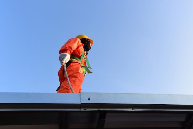 Werknemer in veiligheidsharnas op hoge bouwplaats.
