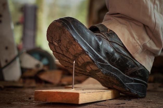 Werknemer in veiligheidsschoenen die op spijkers aan boord van hout in het bouwgebied stappen