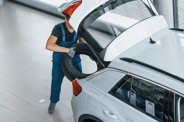 Werknemer in zwart en blauw uniform plaatst auto wiel binnenkant van witte auto