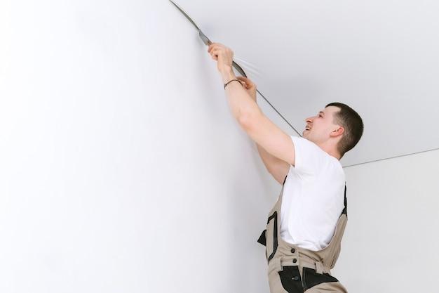 Werknemer installeert een spanplafond. bouw- en renovatieconcept