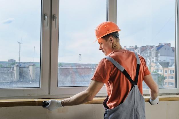 Werknemer installeert een vensterbank.