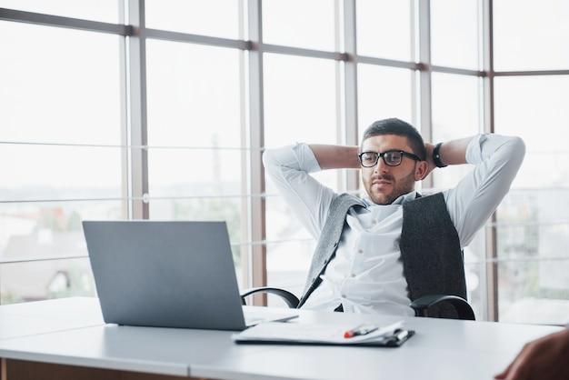 Werknemer is een jonge man met een laptop op kantoor.