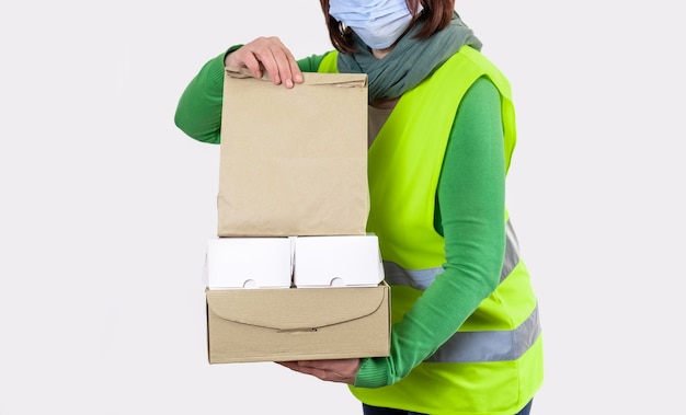 Werknemer is in een groen vest met veel kartonnen dozen, leveringsconcept.