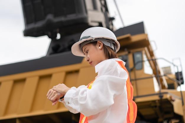 Werknemer kijken horloge op pols in bruinkool of kolenwinning met de vrachtwagen die kolen vervoert.