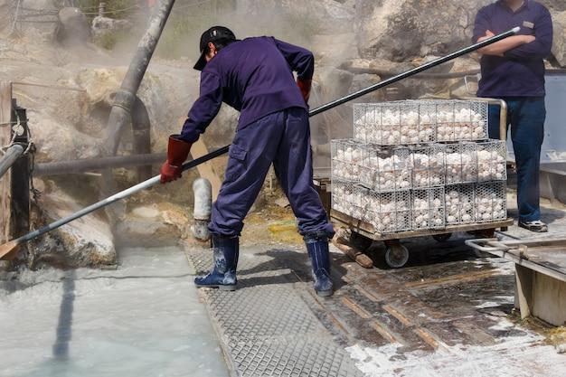Werknemer kookt eieren in mineraalwater in owakudani-vallei