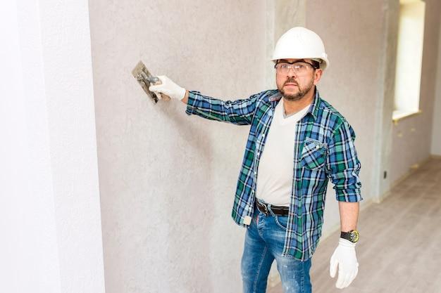 Werknemer maakt decoratieve gips op de muur-man