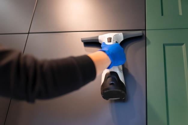 Werknemer maakt keuken schoon met raamstofzuiger