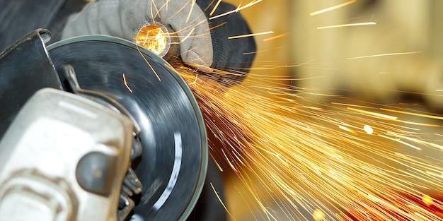 Werknemer maakt metalen stalen buis slijpen, close-up vele vonken