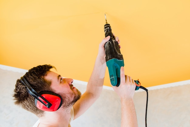 Werknemer maakt reparaties en boren in het plafond