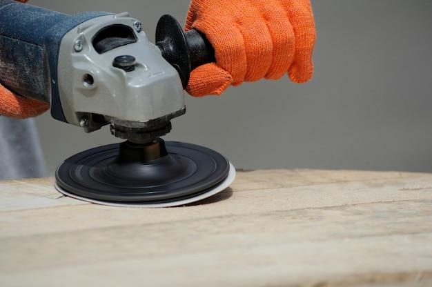 Werknemer maalt het hout van een haakse slijpmachine