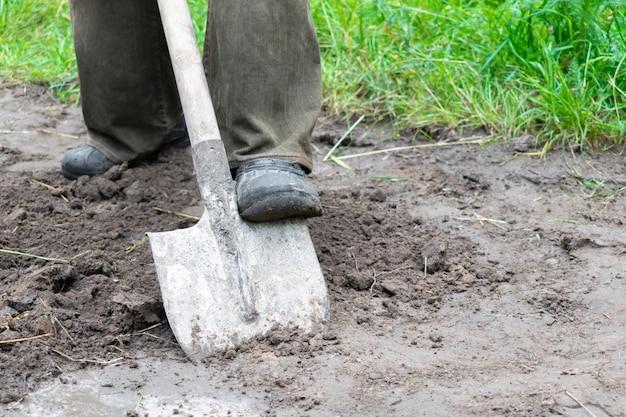 Werknemer man graven bodem, grond met schop in rubberen laarzen in de tuin, close-up.