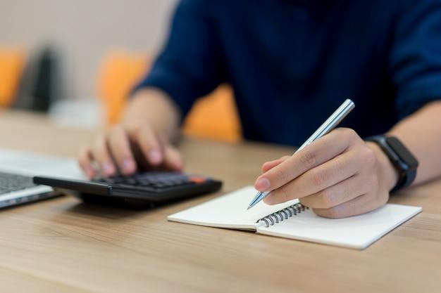 Werknemer man hand schrijven op laptop en druk op de rekenmachine