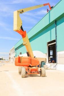 Werknemer man op een schaar hydraulische heftafel platform naar een fabrieksdak