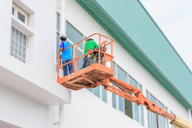 Werknemer man op een scissor hydraulische heftafel platform naar een fabrieksdak op constructi