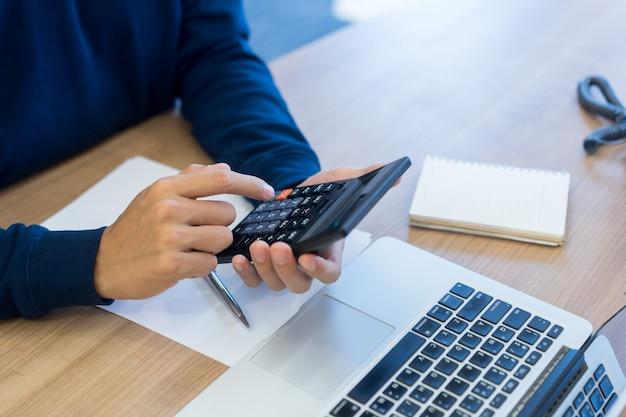 Werknemer man vinger hand druk op rekenmachine