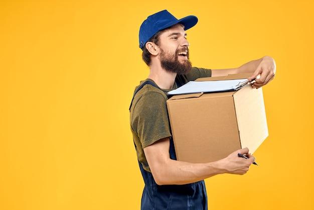 Werknemer mannelijke koerier dozen verpakking documenten gele muur leveren.