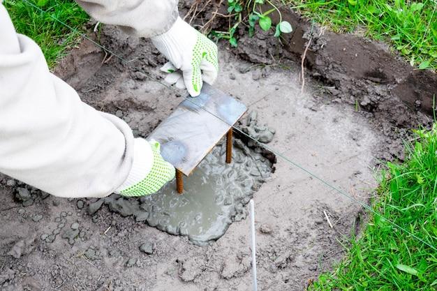 Werknemer mans handen in handschoenen hamer ijzeren constructie in cementoplossing, drijfmest, betonmortel. voorbereiding voor bouwproces, renovatie, huisfundering.