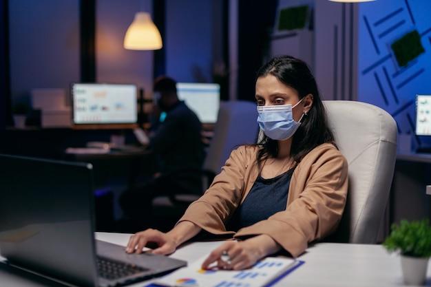 Werknemer met beschermend gezichtsmasker die 's avonds laat werkt in een nieuw normaal kantoor. vrouw die regels voor sociale afstand volgt als gevolg van een coroanvirus-pandemie terwijl ze tot laat op kantoor werkt.