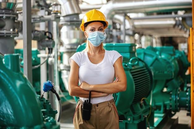Werknemer met beschermende helm en gezichtsmasker op staande in verwarmingsinstallatie met gekruiste armen.