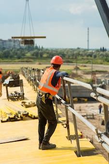 Werknemer met beschermende helm op de bouwplaats van een transportbrug