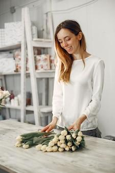 Werknemer met bloemen. vrouw maakt een boeket. leuk meisje aan het werk