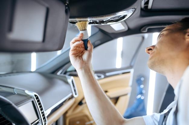 Werknemer met borstel veegt auto-interieur, stomerij en detaillering