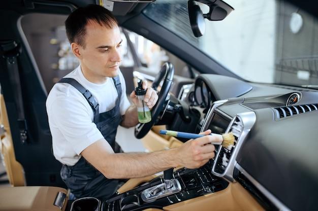 Werknemer met borstel veegt auto luchtkanaal rooster, stomerij en detaillering