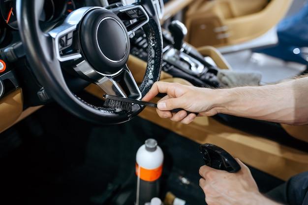Werknemer met borstel veegt auto stuurwiel, stomerij en detaillering