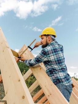 Werknemer met bouwvakker die het dak van het huis bouwt