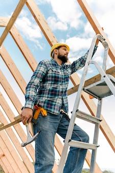 Werknemer met bouwvakker en hamer die een huis bouwt