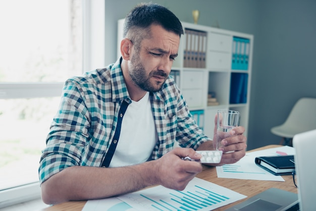 Werknemer met een blauw geruit overhemd die op kantoor werkt