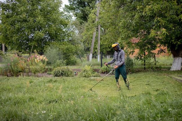 Werknemer met een gasmaaier in zijn handen, gras maaien voor het huis. trimmer in de handen van een man. tuinman die het gras maait. levensstijl.