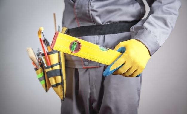 Werknemer met een gereedschapsriem vasthoudniveau
