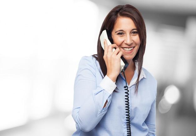 Werknemer met een grote glimlach te praten over de telefoon