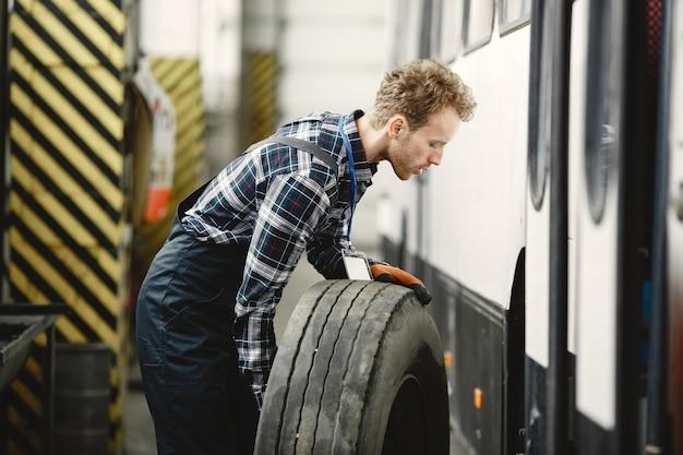 Werknemer met een wiel. wiel vervangen. man in uniform