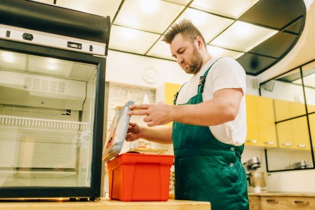 Werknemer met gereedschapskist reparatie koelkast thuis. reparatie van koelkastbezetting, professionele service